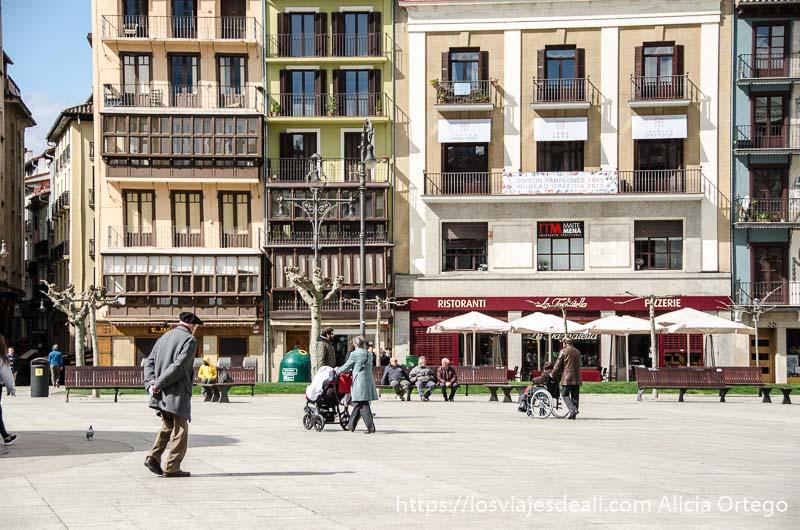 plaza de pamplona con anciano con boina y gabardina gris cruzándola