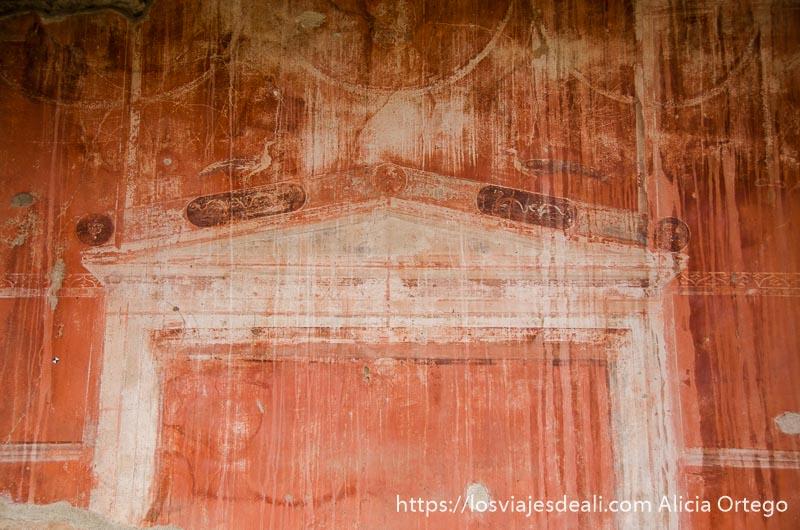 pared pintada de rojo con dibujo de pórtico visita a herculano italia