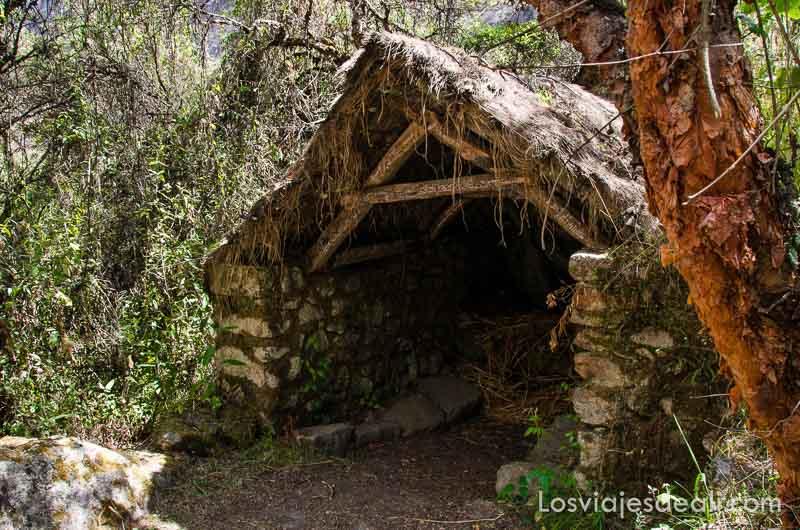 cabaña con muros d epiedra y techo a dos aguas de madera y paja