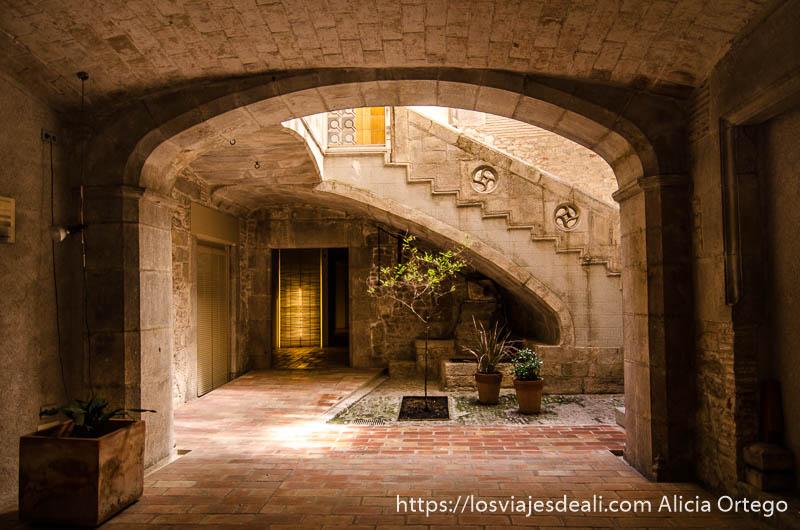 patio medieval de entrada a una casa con escaleras al fondo en girona