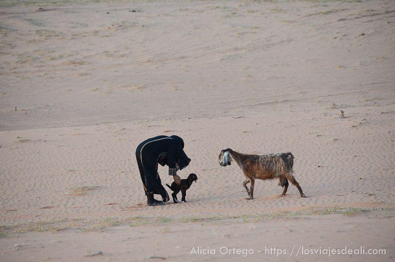 beduina y su cabra en desierto de wadi rum