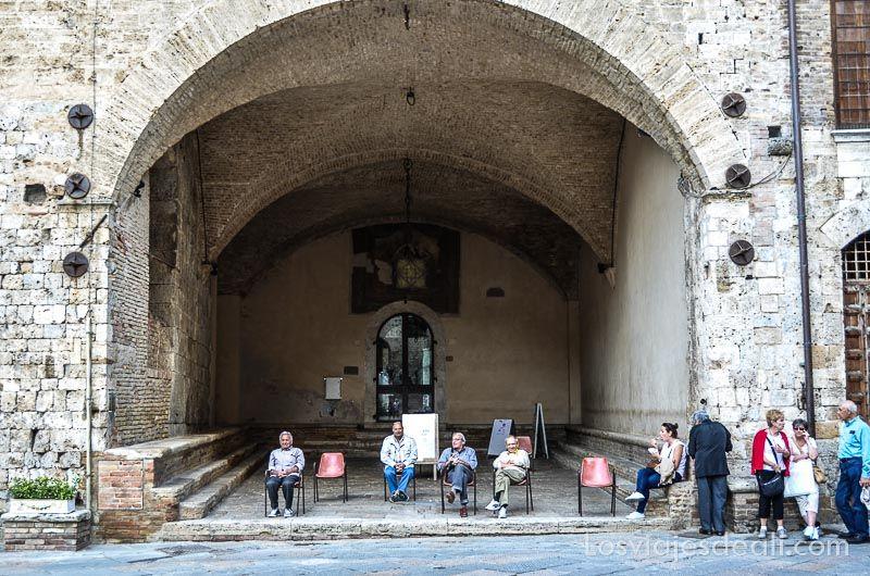 gran portalón rematado con arcos de medio punto y señores del pueblo sentados bajo el mismo en sillas sencillas