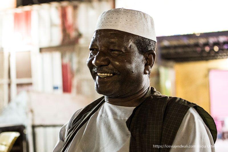 retrato de seif sonriendo con su gorrito blanco bordado gentes de Sudán