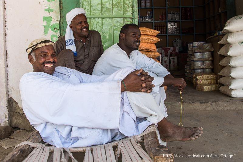 tres hombres sentados en un camastro sonríen mientras charlan con nosotros gentes de sudán