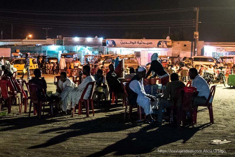 plaza de Karima por la noche llena de hombres sentados al fresco tomando té