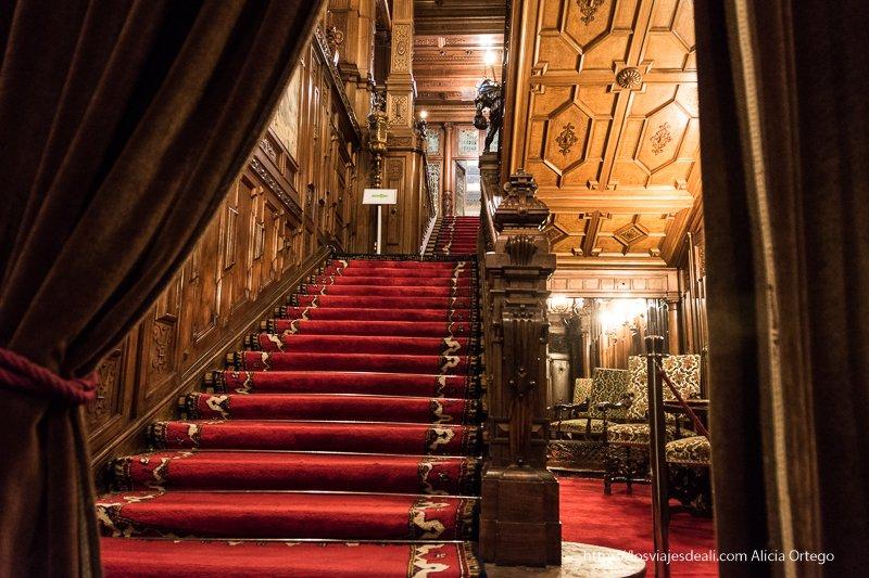 escaleras con alfombra roja y techos de madera en el castillo de Peles en sinaia