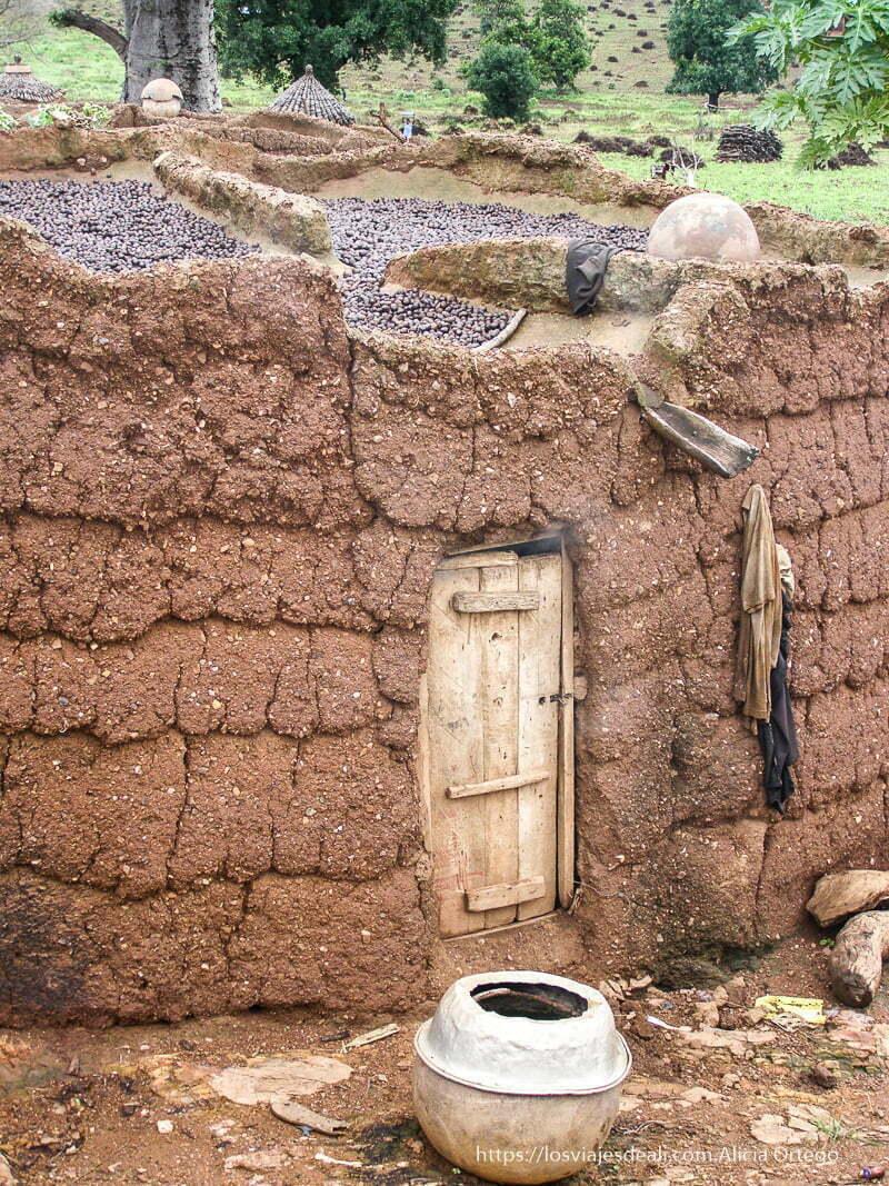 casa de adobe de sansana con frutos secándose en el tejado Burkina