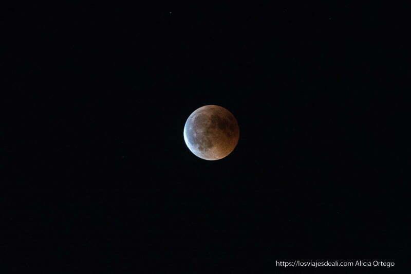 luna llena con color rojo y azulado según sale del eclipse