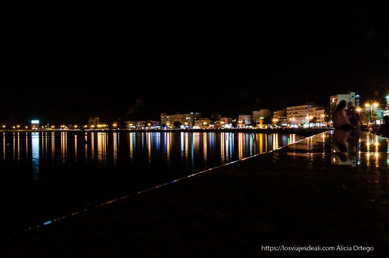 corniche de muscat con las luces reflejándose en el agua