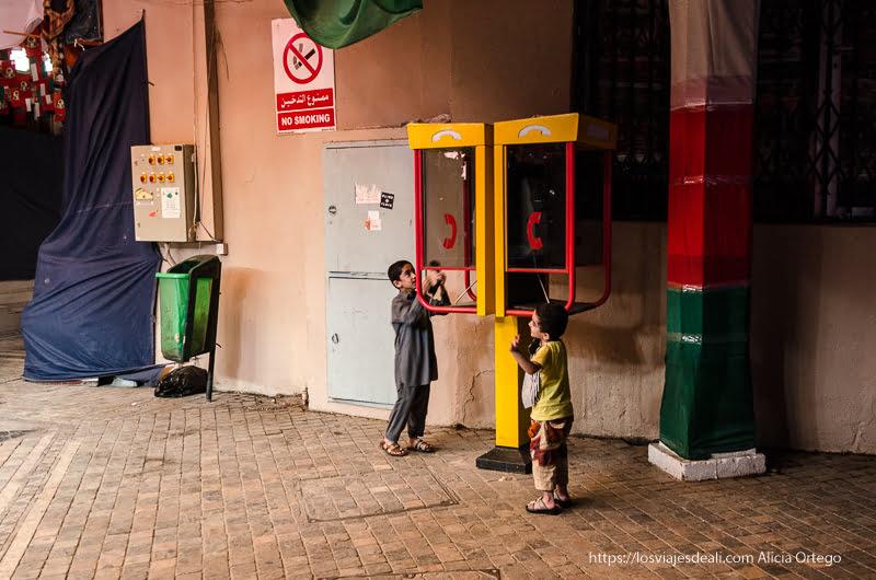 niños jugando con cabinas telefónicas en Muscat