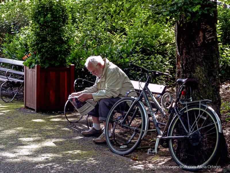 hombre leyendo el periódico junto a su bicicleta en un parque de dublin