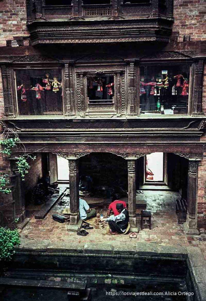 patio con balcones de madera labrada y artesanos de marionetas trabajando nepal