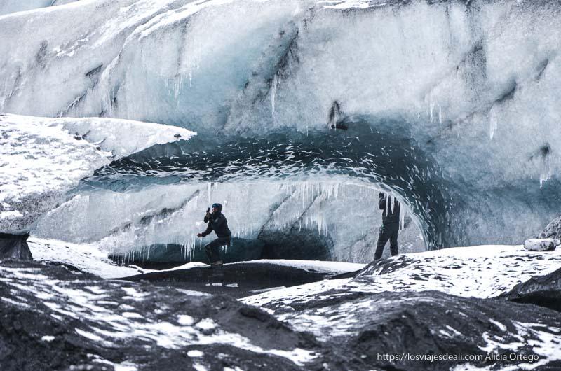 dos hombres bajo un gran arco de hielo de color azul