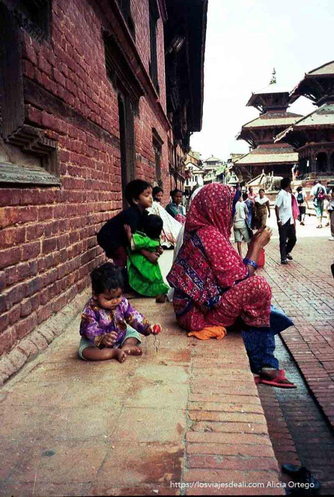 muer sentada con sari rojo y sus niños alrededor en patan nepal