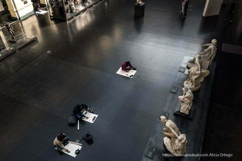vista del patio de bellas artes desde segundo piso con tres estudiantes dibujando en el suelo las estatuas