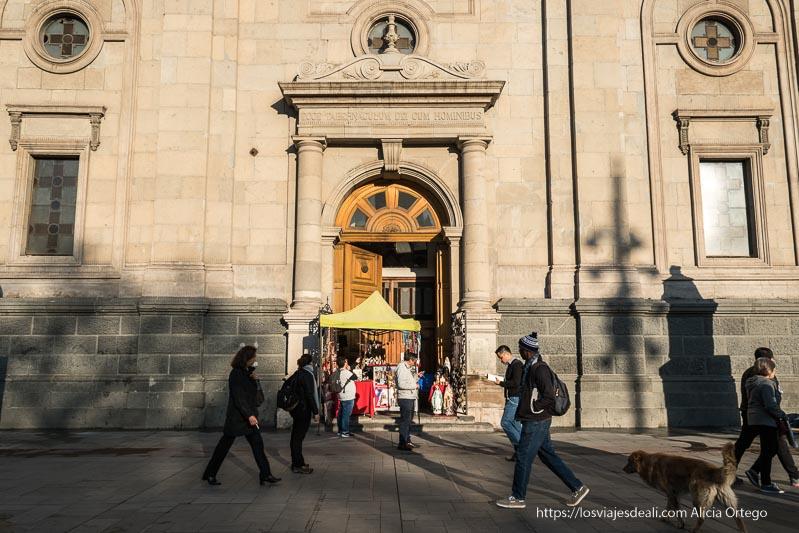puerta secundaria de la catedral de santiago de chile con gente pasando delante