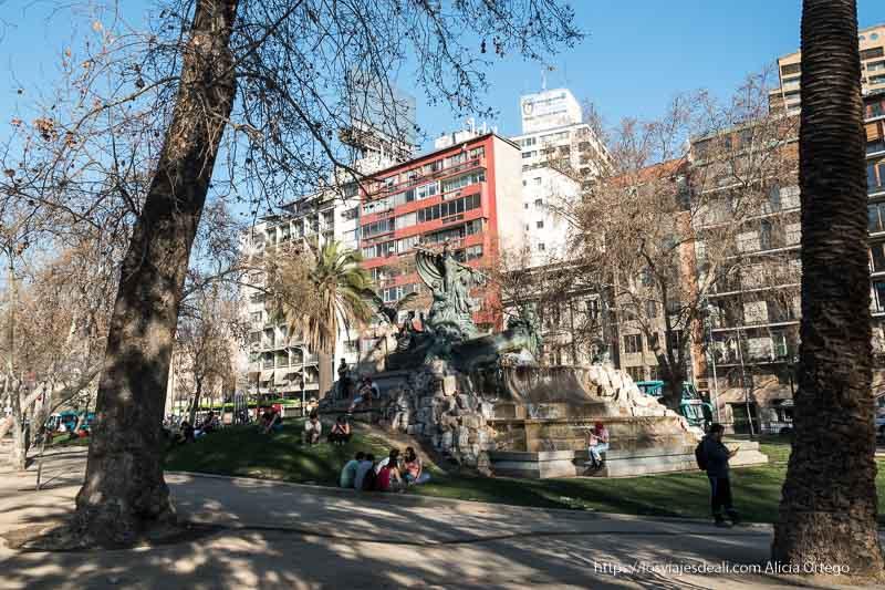 parque de santiago de chile con gran estatua y fuente y jóvenes sentados en la hierba