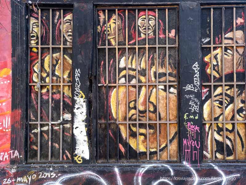 mural de indígenas encarcelados pintado en una ventana del barrio brasil de santiago de chile