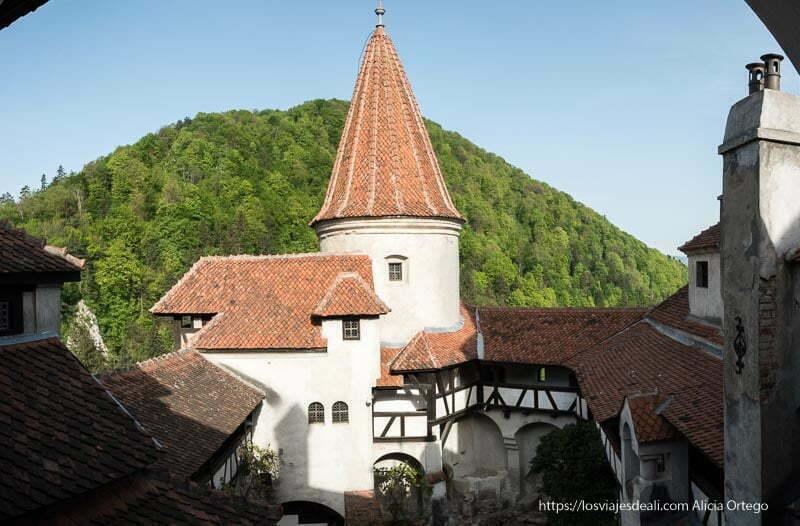 patio del castillo de bran con torre circular paredes encaladas y tejados de teja roja