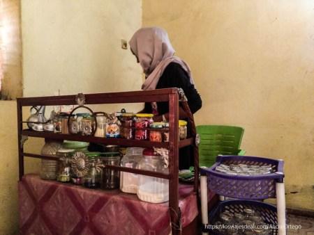tea lady joven en su puesto de té con botes de especias