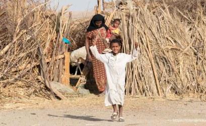 niño nubio saliendo del corral de las cabras con brazos en alto saludando lleva una yalabía blanca detrás su madre con bebé