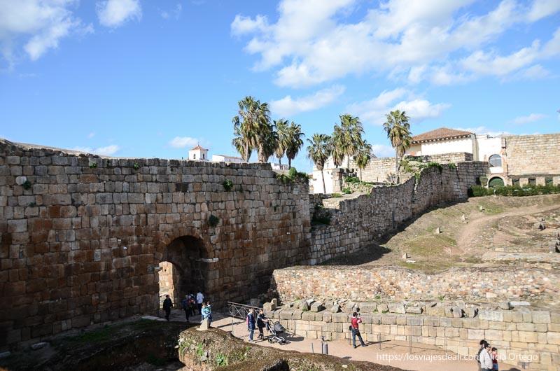 vista de la puerta de la alcazaba de mérida con palmeras al fondo
