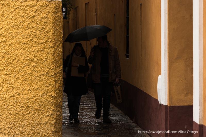 pareja andando por callejón muy estrecho de santa cruz con paredes pintadas de ocre planes en sevilla