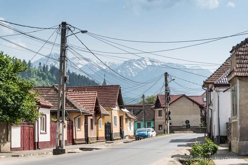 calle de Rasnov con casitas pintadas de colores y tejados muy inclinados con montañas al fondo
