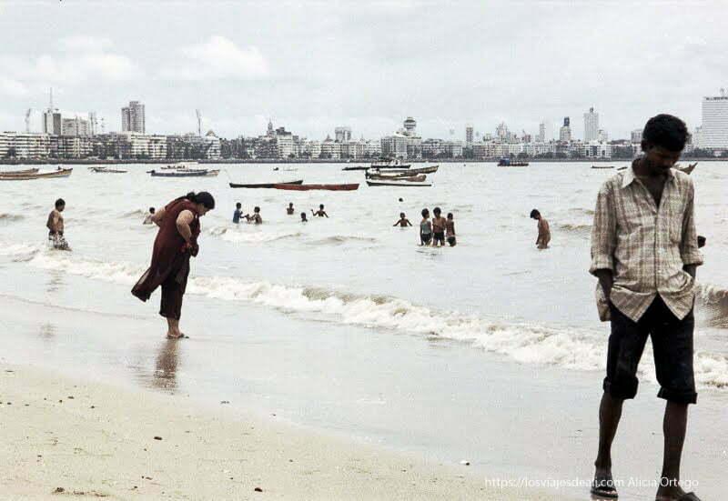 hombre paseando por orilla en playa de bombay y mujer detrás bombay