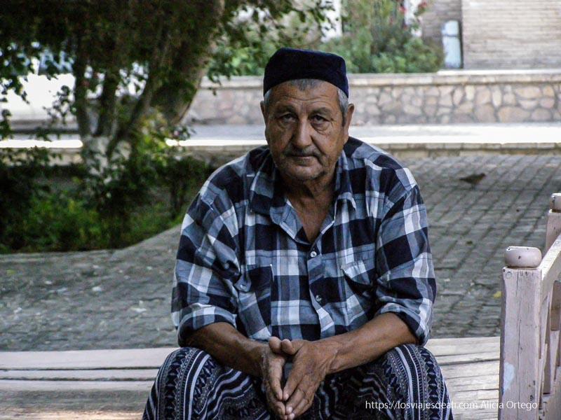hombre sentado a la sombra mirando a la cámara en bukhara