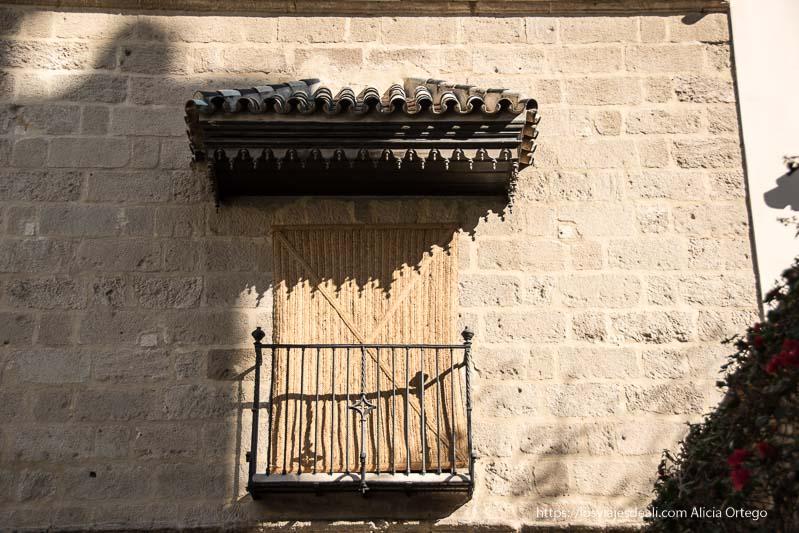 balcón con persiana de esparto en casa de picasso en centro de málaga