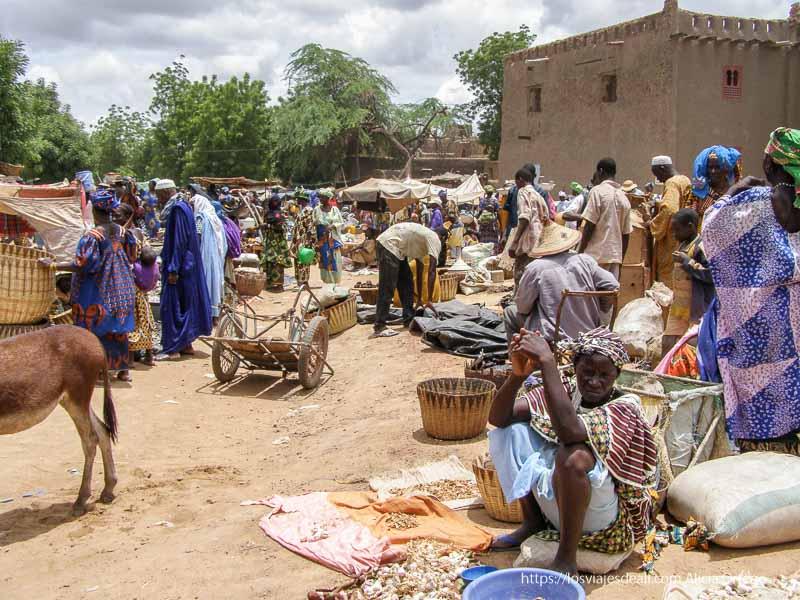 puestos en el suelo, carros, gente vestida de colores, burritos djenne en su dia de mercado