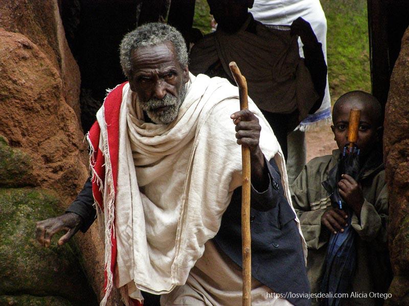 un anciano con su bastón y manto alrededor de cuello y hombros llega a las lalibela