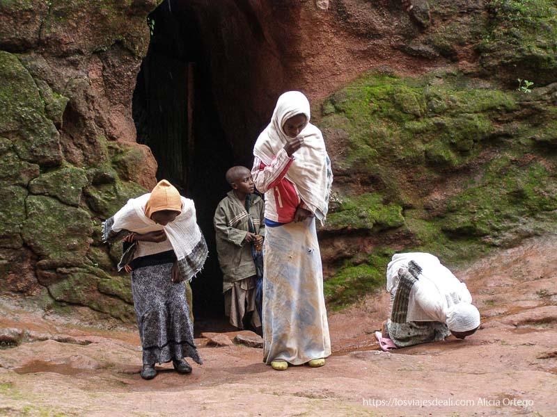 tres niñas se inclinan ante la iglesia, una de ellas besando el suelo iglesias de lalibela