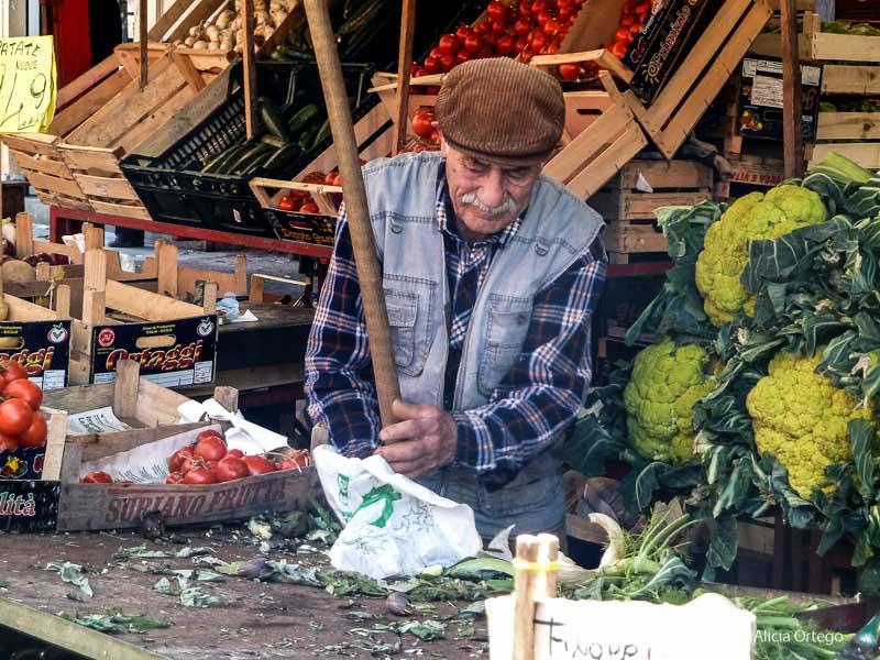 señor con gorra de pana en puesto de coliflores iglesias y mercados de palermo