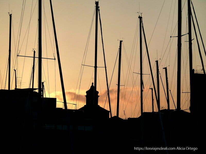 puesta de sol con campanario de iglesia entre postes de barcos iglesias y mercados de palermo