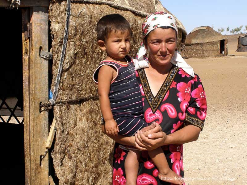 mujer con su hijo en brazos en el desierto khiva