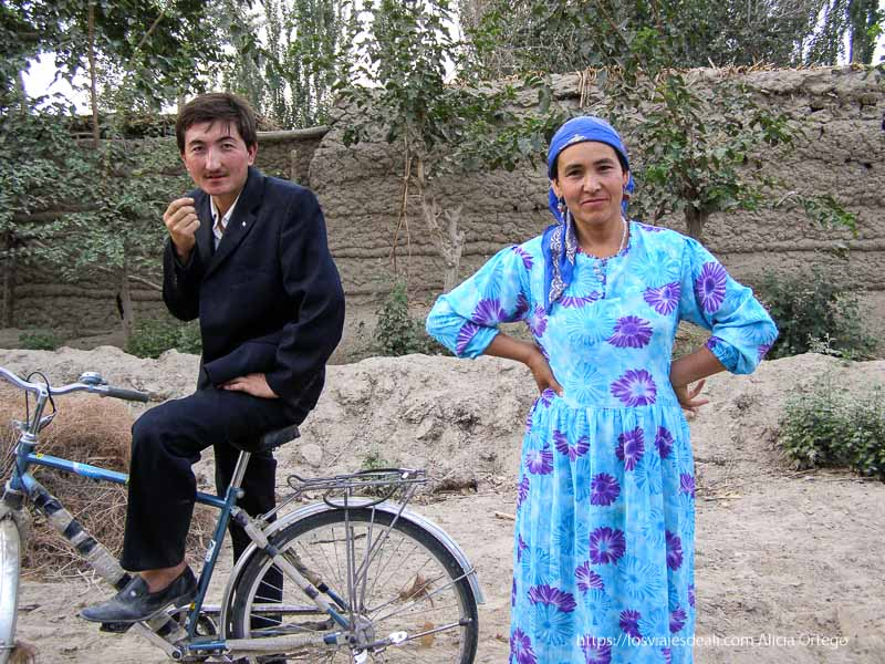 mujer vestida de azul y hombre con traje negro montado en bici vieja oasis de yarkand