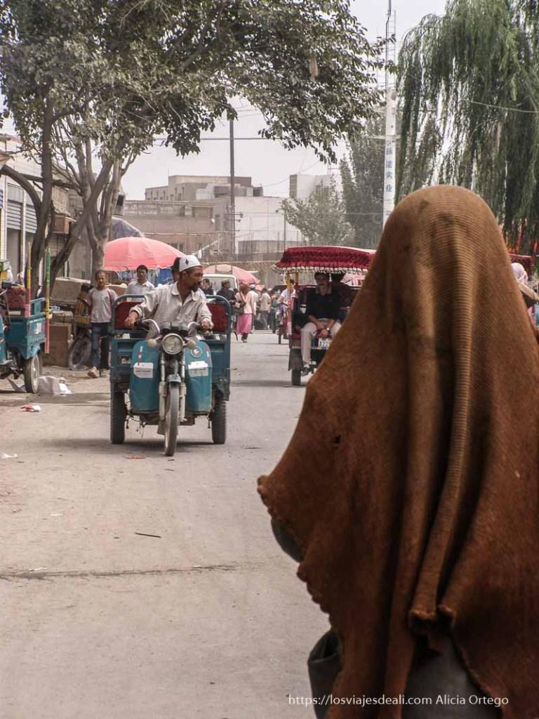 mujer andando con tela de rejilla cubriendo rostro en oasis de yarkand