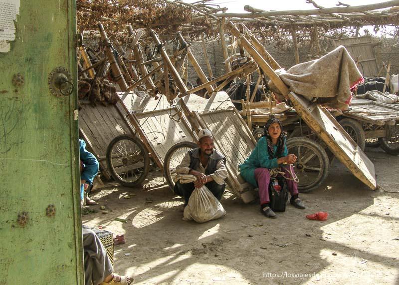 carros de mercancías aparcados y una pareja sentados oasis de yarkand