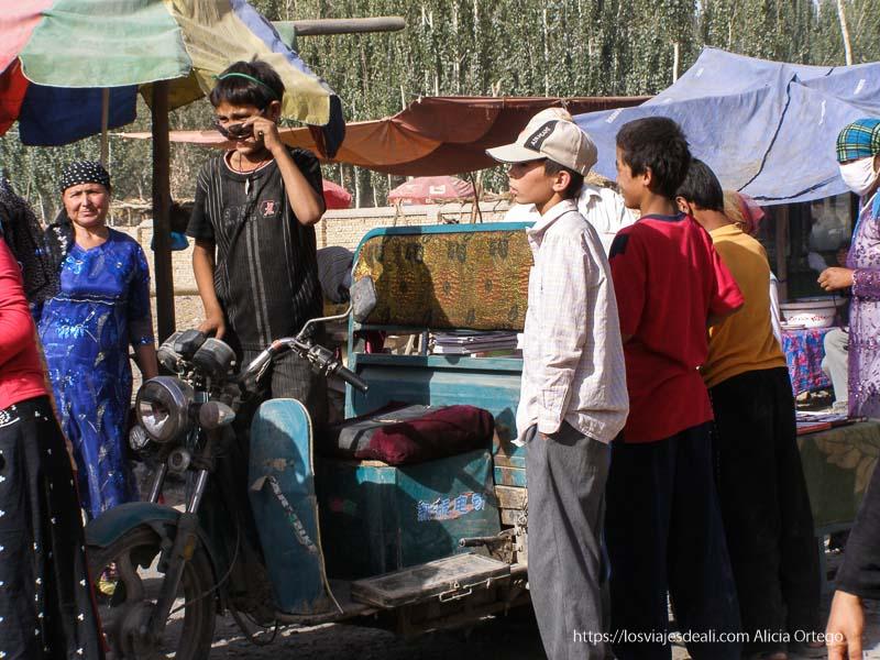 niño en motocarro con otros alrededor oasis de yarkand