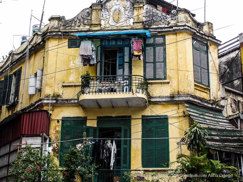 casa colonial muy envejecida con persianas verdes qué ver en hanoi
