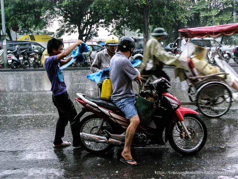 motoristas poniéndose capas de plástico a toda prisa por la lluvia qué ver en hanoi