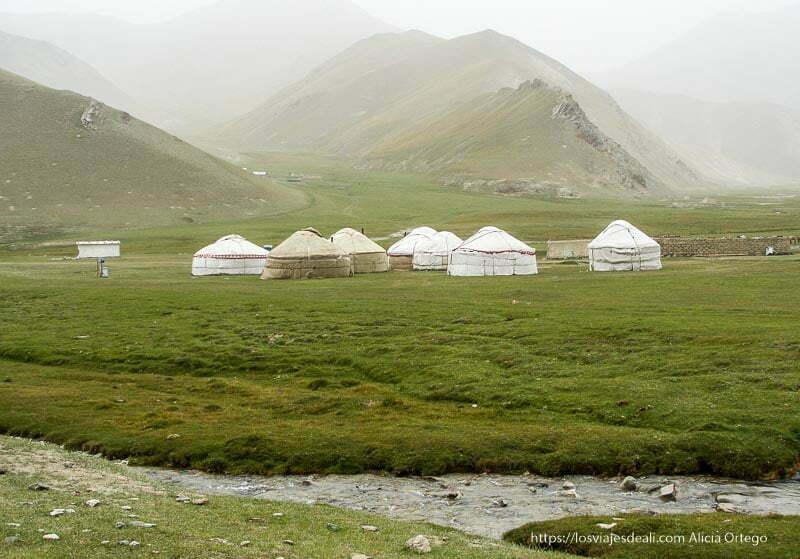 campamento de yurtas con montañas entre niebla tash rabat