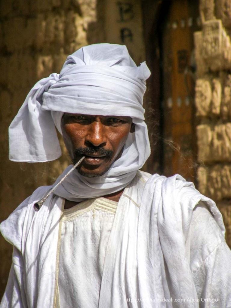 hombre de tombuctú vestido de blanco fumando pipa