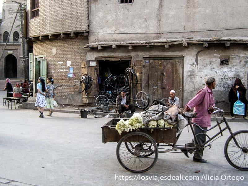 hombre pasando con su carro de mercancías y bicicleta ante un taller de bicis en la vieja kashgar en la ruta de la seda