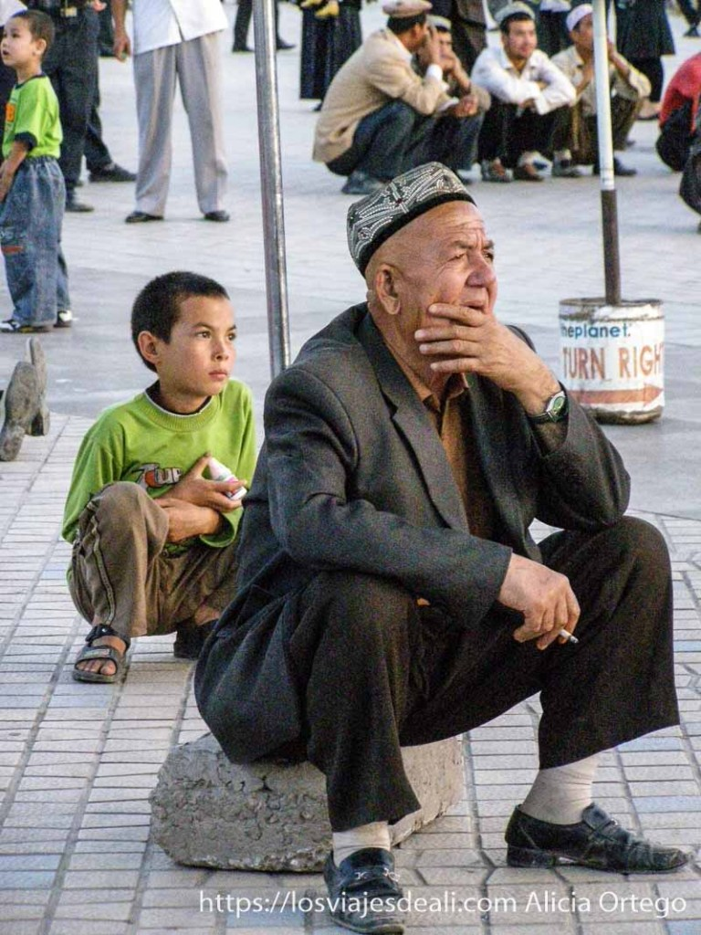 hombre y niño mirando una película en la calle kashgar en la ruta de la seda