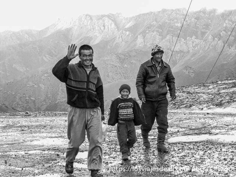dos hombres y un niño caminando por la carretera helada campo base del pico lenin