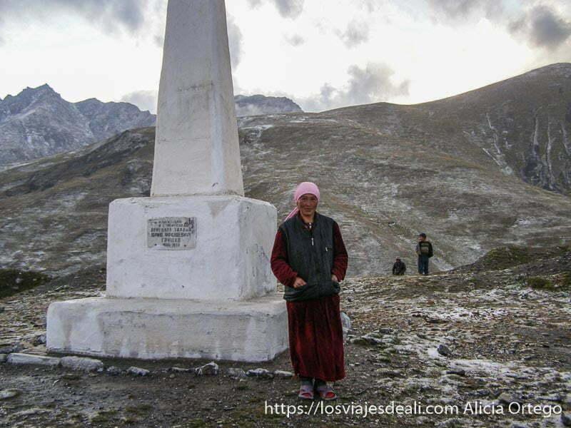 mujer con pañuelo rosa en la cabeza junto al hito del puerto de montaña campo base del pico lenin