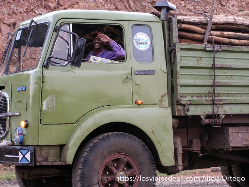 camionero saludando desde la cabina, lleva madera, de camino al lago chamo
